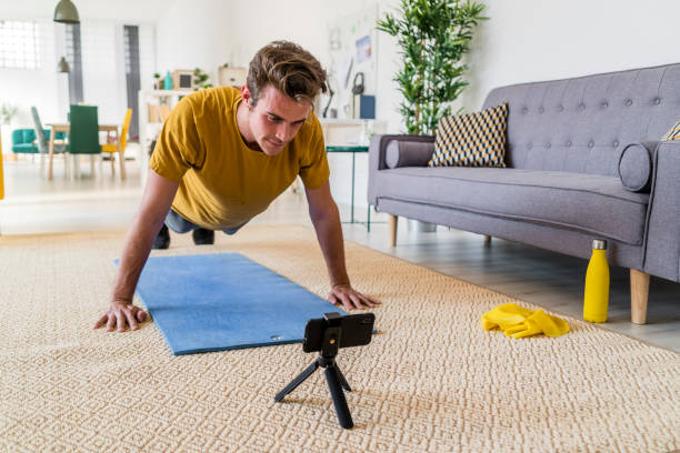 Young man looking at mobile phone while exercising on mat at home