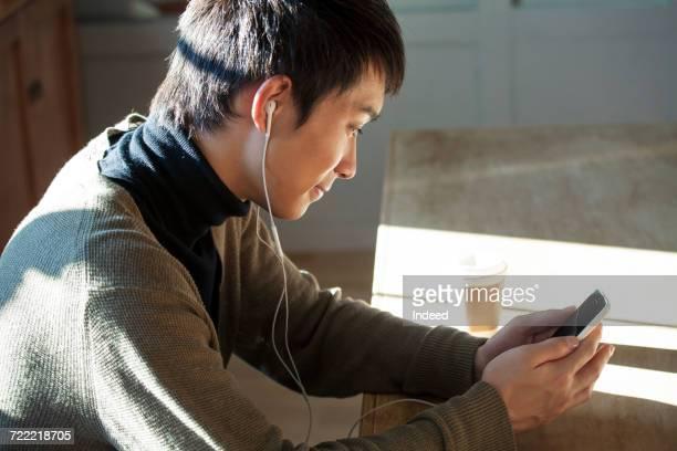 Young man looking at MP3 player at table