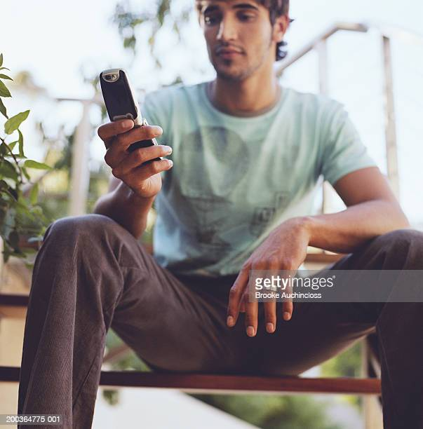 Young man looking at screen on mobile phone