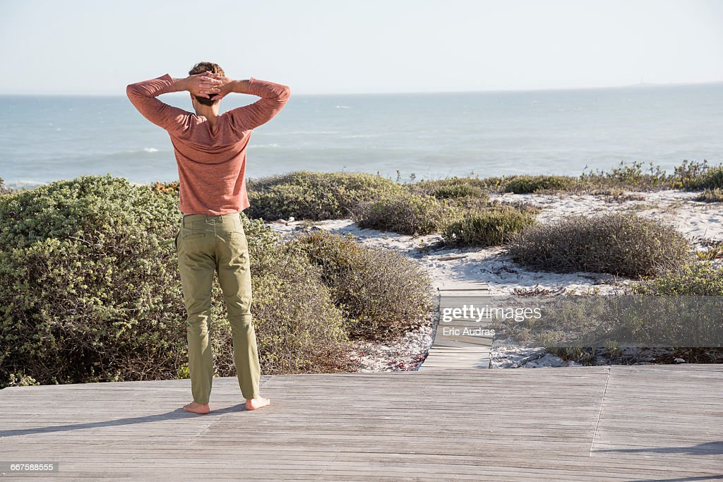 Young man looking at sea on the beach : Stock Photo