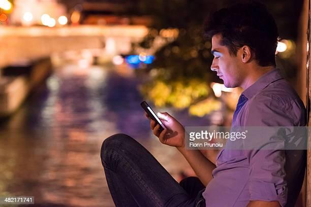 Young man looking at smartphone at night, Paris, France
