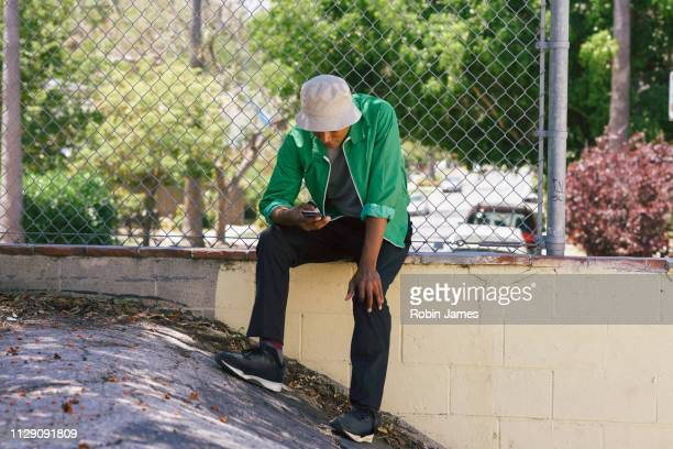 young man looking at smartphone by park fence, los angeles, california, usa - チューリップ帽 ストックフォトと画像