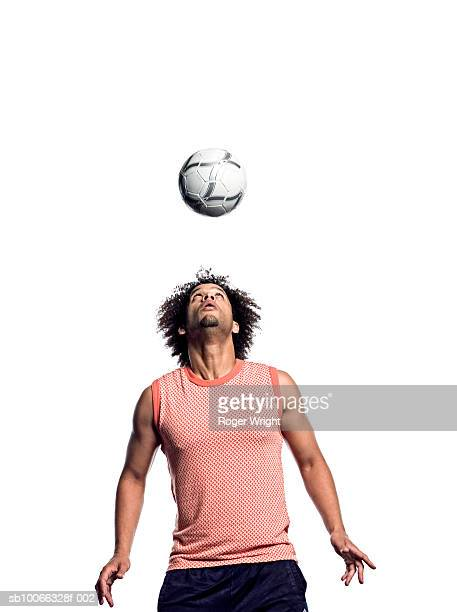 Young man looking at soccer ball thrown in mid-air