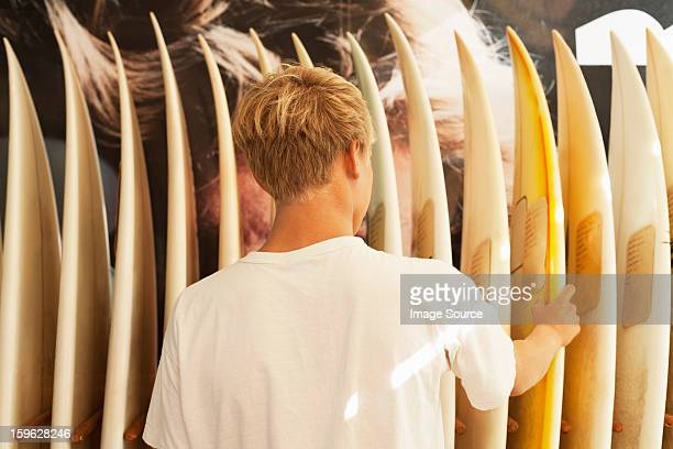 Young man looking at surfboards