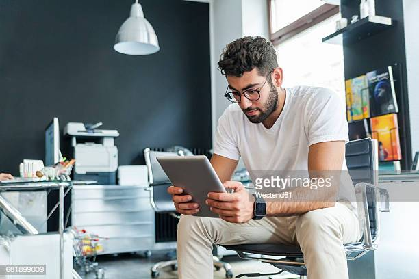 young man looking at tablet in a modern office - smart watch stock pictures, royalty-free photos & images