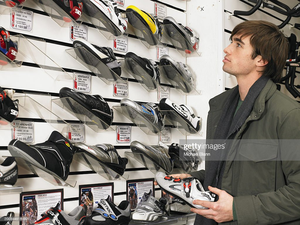 Young man looking at trainers in shoe shop, side view : Stock Photo
