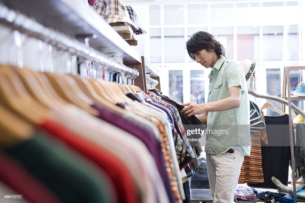 Young man looking at T-shirt in store : Stock Photo