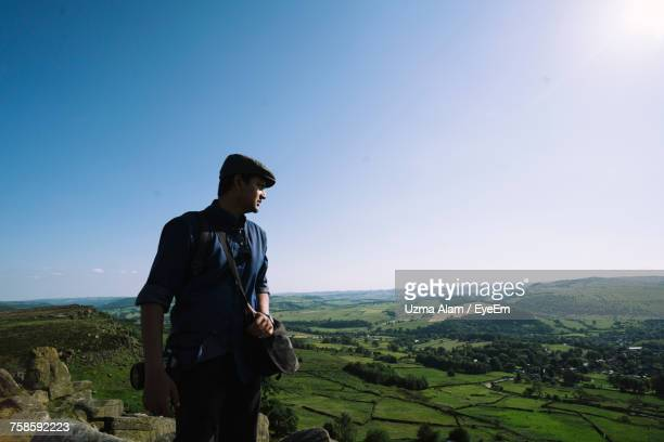 Young Man Looking At View While Hiking On Mountain Against Sky