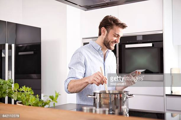 Young man looking at with mini tablet while cooking