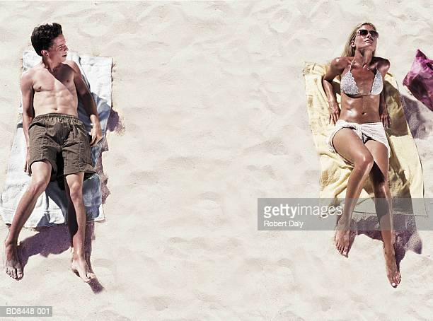 young man looking at woman sunbathing on beach, elevated view - ammirazione foto e immagini stock