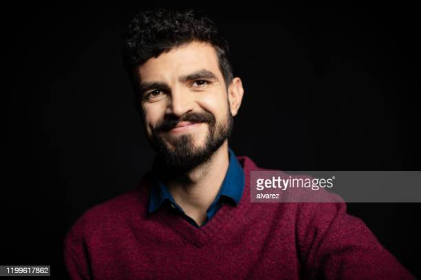 junger mann schaut weg und grinst - nordafrikanischer abstammung stock-fotos und bilder