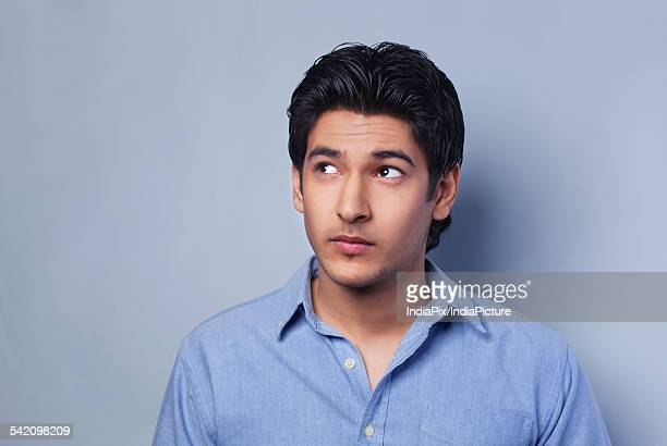 Young man looking away over colored background