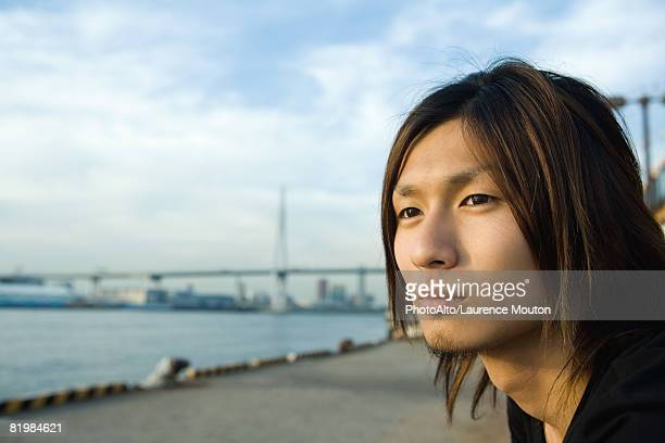 Young man looking away, waterfront in background