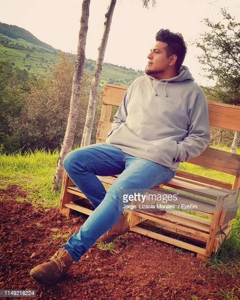 young man looking away while sitting on bench against sky - tlaxcala state stock photos and pictures