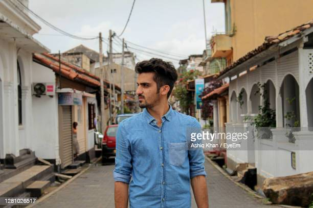 young man looking away while standing against buildings - sri lanka stock pictures, royalty-free photos & images