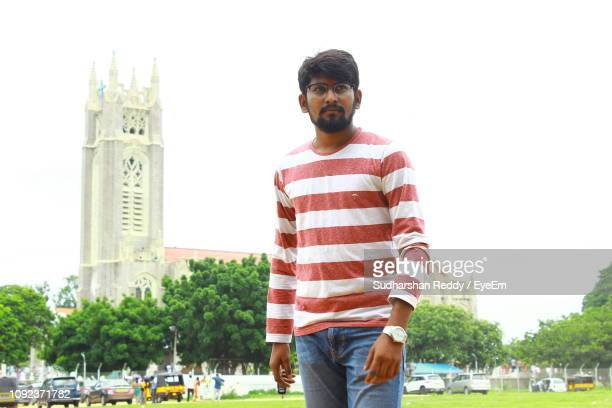 young man looking away while standing against tower in city - striped shirt stock pictures, royalty-free photos & images