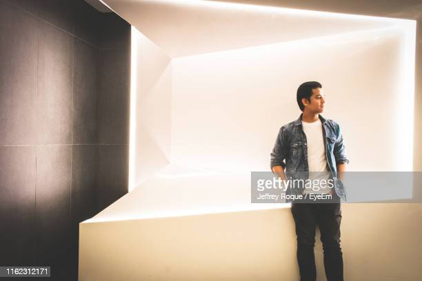 young man looking away while standing against wall - jeffrey roque stock photos and pictures
