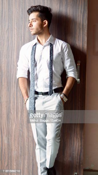 young man looking away while standing door - trousers stock pictures, royalty-free photos & images