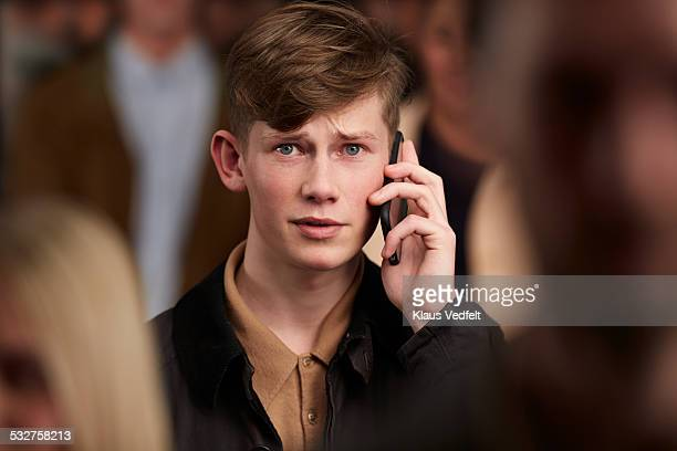 young man looking concerned on the phone - mensen op de achtergrond stockfoto's en -beelden