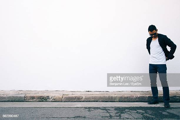 Young Man Looking Down Standing Against White Wall