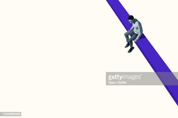 young man looking down while sitting on blue ramp - vulnerability stock pictures, royalty-free photos & images