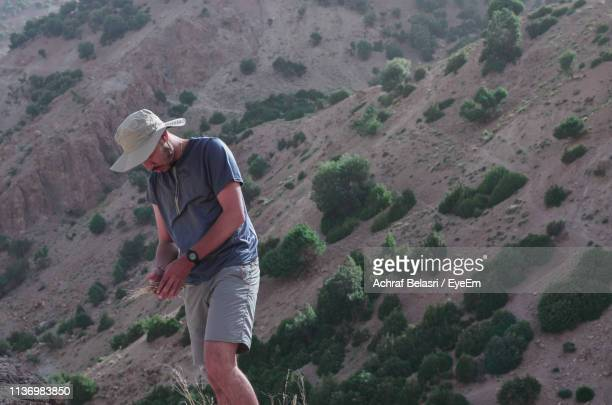Young Man Looking Down While Standing Against Mountain