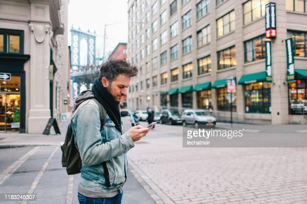 ニューヨーク州マンハッタンでライドシェアを探している若者 - 迷う ストックフォトと画像