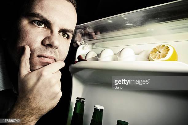 Junger Mann auf der Suche nach Essen in Kühlschrank-grunge-Stil