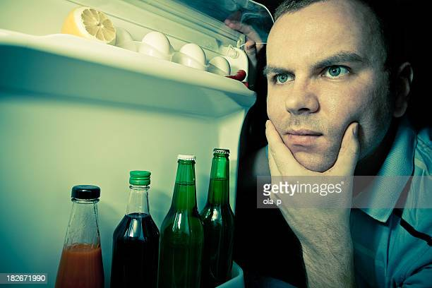 Young man looking for food in refrigerator
