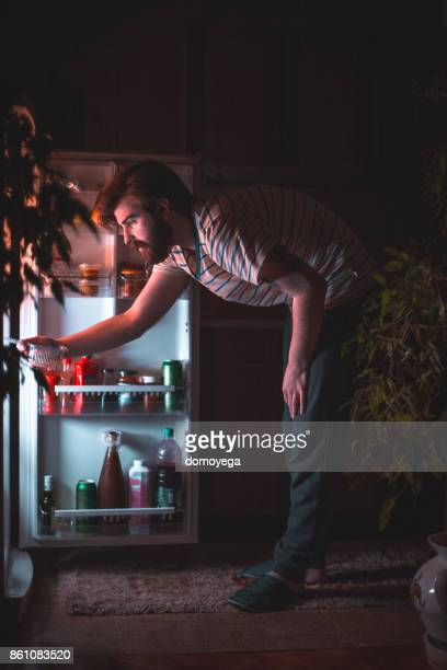young man looking for what to eat late night - unhealthy living stock pictures, royalty-free photos & images