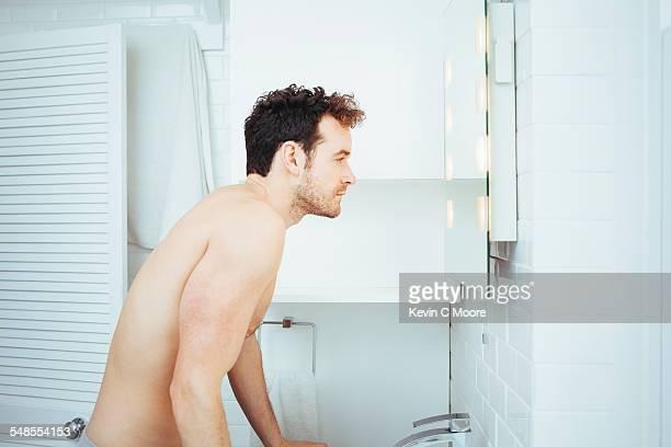 Young man looking in bathroom mirror