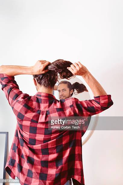 Young man looking in mirror, putting hair in ponytail, rear view