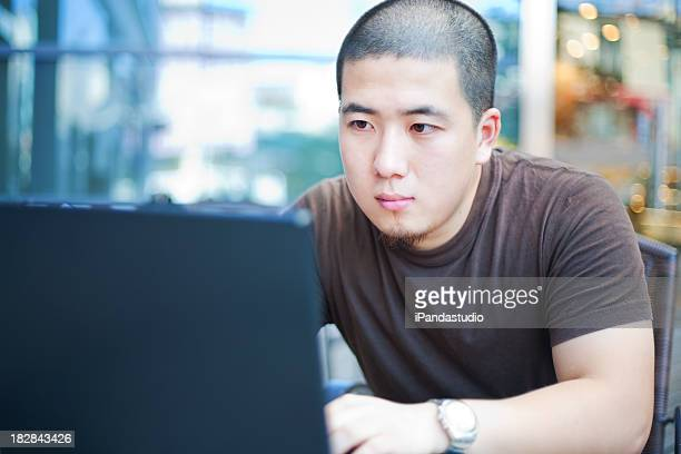 Young man looking intently at his laptop in a cafe