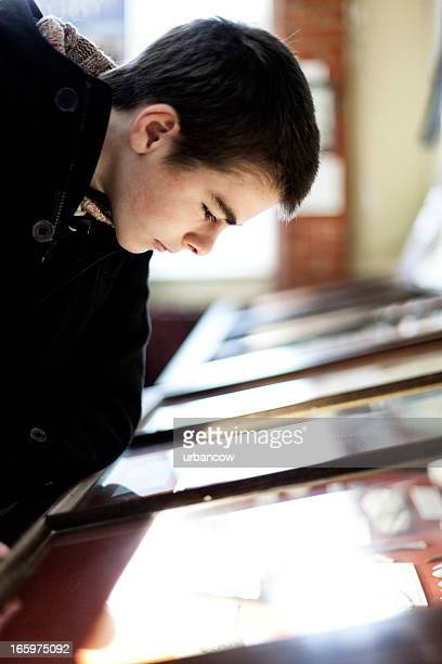 Young man looking into a display cabinet