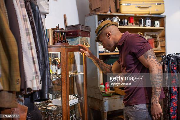 Young man looking into cabinet in vintage shop