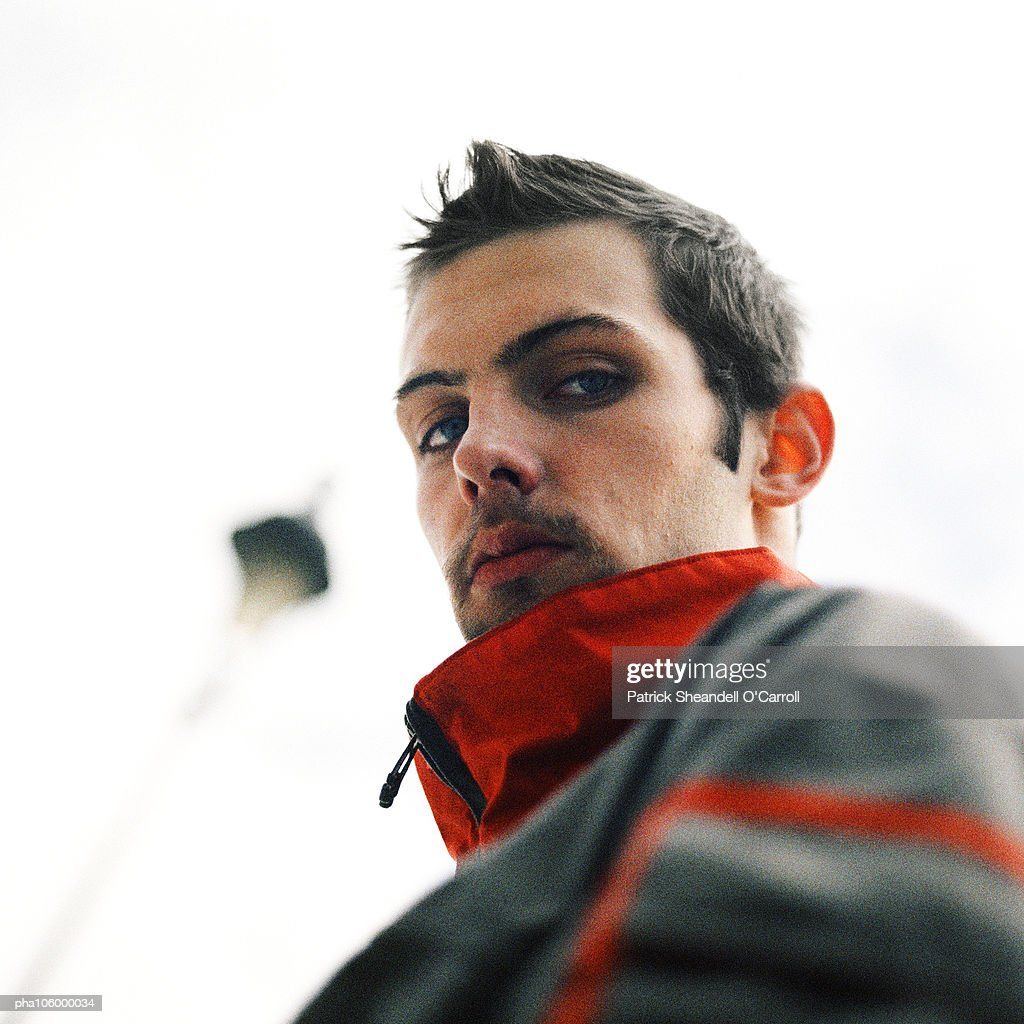 Young man looking into camera, close-up, low angle view : Stockfoto