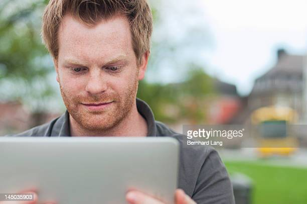young man looking on tablet computer - newtechnology stock pictures, royalty-free photos & images
