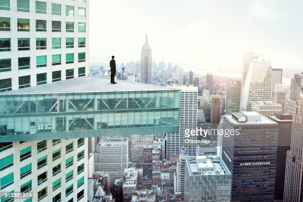 young man looking out at city skyline in new york - grattacielo foto e immagini stock