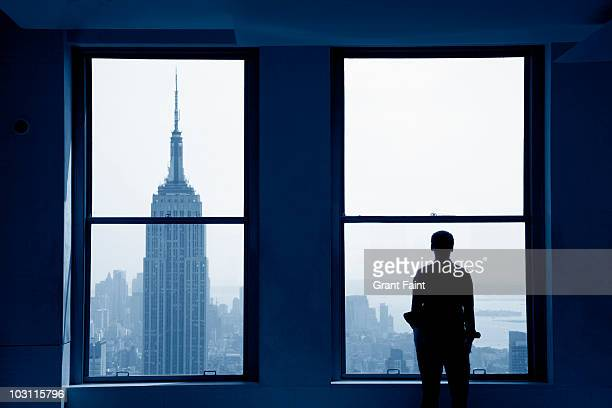 young man looking out at manhattan skyline - looking at view foto e immagini stock