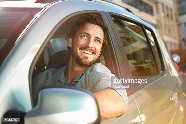 young man looking out of car window - gelassene person stock-fotos und bilder