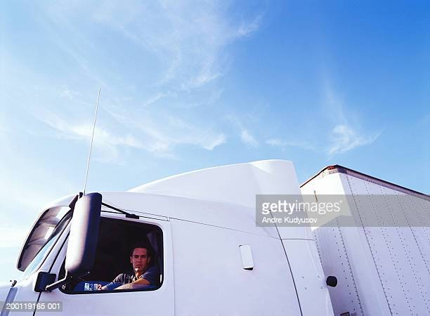 Young man looking out of driver's side window of semi-truck, portrait