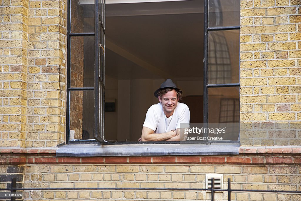 young man looking out of his window : Stock-Foto
