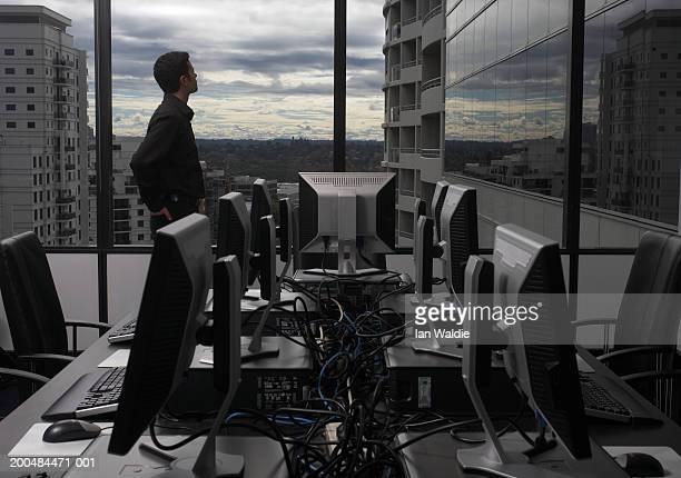 Young man looking out of office window