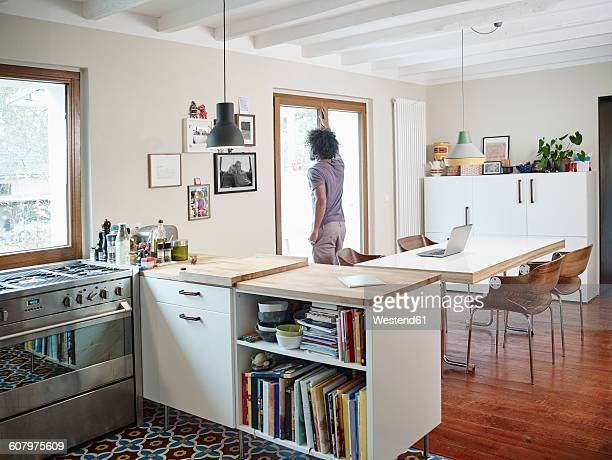 Young man looking out of window in open plan kitchen