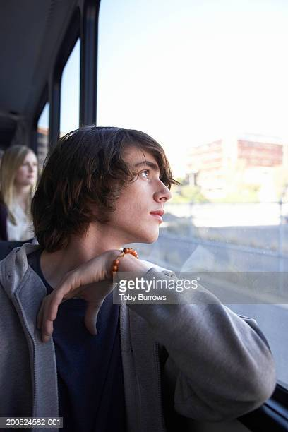 Young man looking out of window of bus