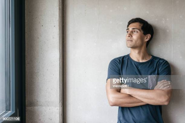 young man looking out of window - beschaulichkeit stock-fotos und bilder