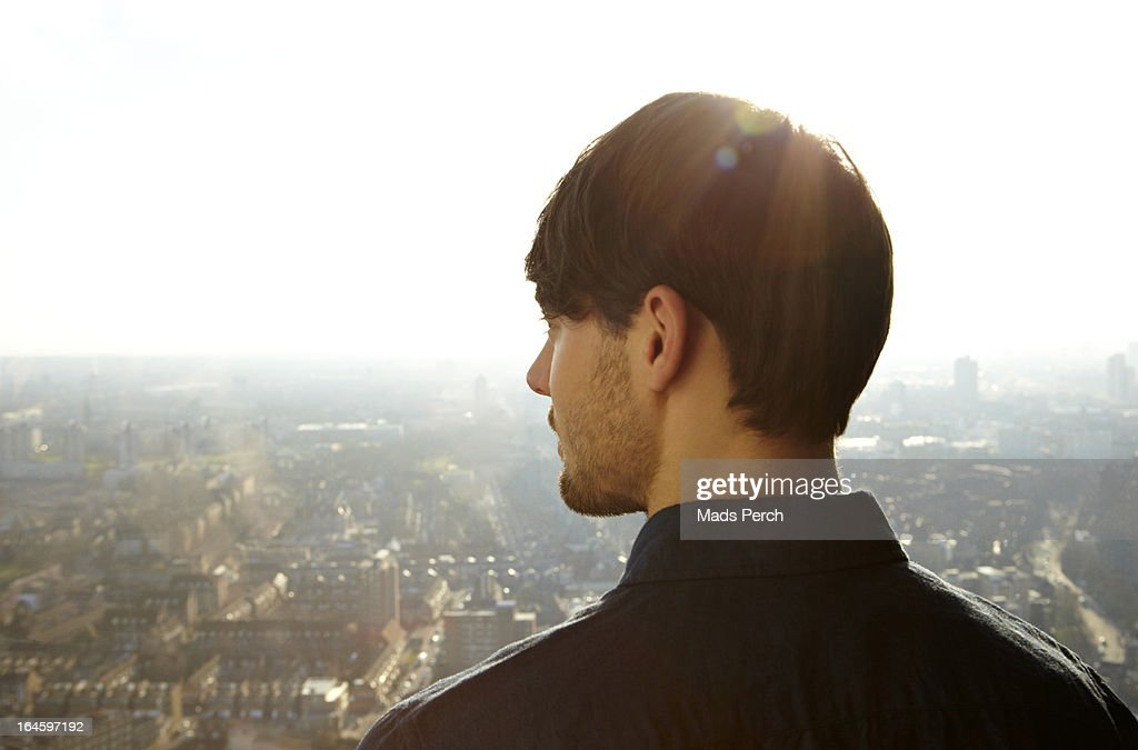 young man looking out on the city : Bildbanksbilder