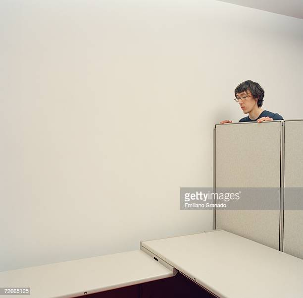 Young man looking over partition wall in empty cubicle