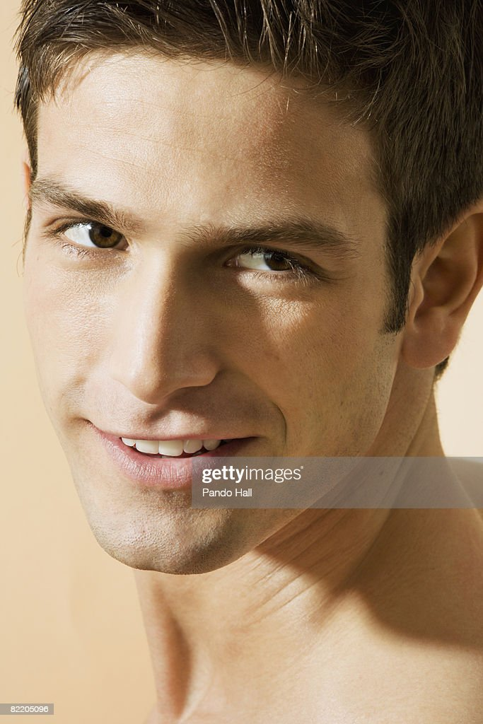 Young man looking over shoulder, smiling, portrait : Stock Photo