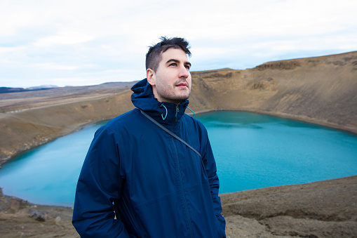 Young man looking over the camera at the Viti crater, in the Krafla volcanic area in Iceland. - gettyimageskorea